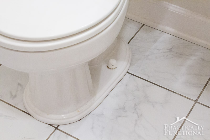 Remove the plastic covers to get at the nuts attaching the toilet to the floor