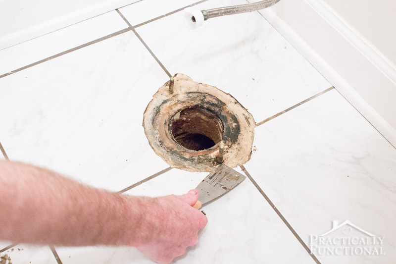 Scrape away all of the wax around the drain and bolts